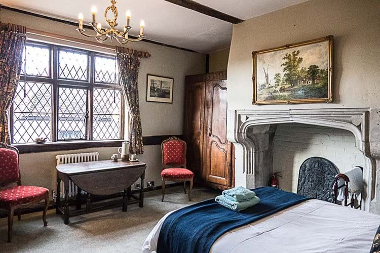 View of stone fireplace in double bedroom