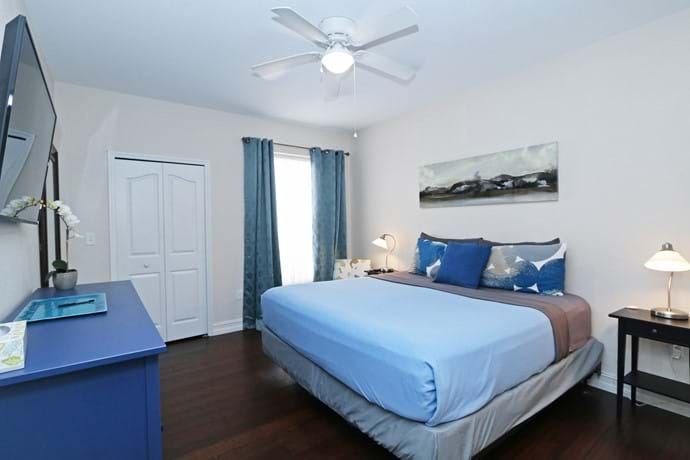 """The Master Bedroom at our 4 bedroom condo with walk in closet, 46"""" TV, chest of drawers, ceiling fan and air con and en suite bathroom"""