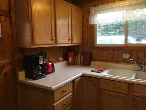 Kitchen area has stove, microwave, coffee maker, refrigerator, blender, mixer, pots, pans, griddle, fry pan, glasses, mugs and all the utensils you should need