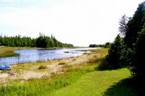 Large front lawn leads to sandy apron that edges the lake water in front of the cottage.