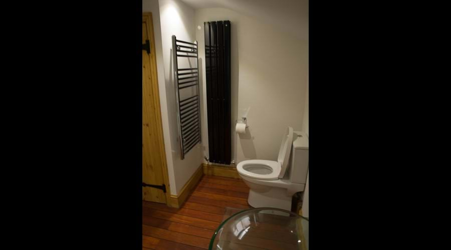 Ship Cottage - Spacious bathroom with ship flooring, modern radiators and wooden cottage doors
