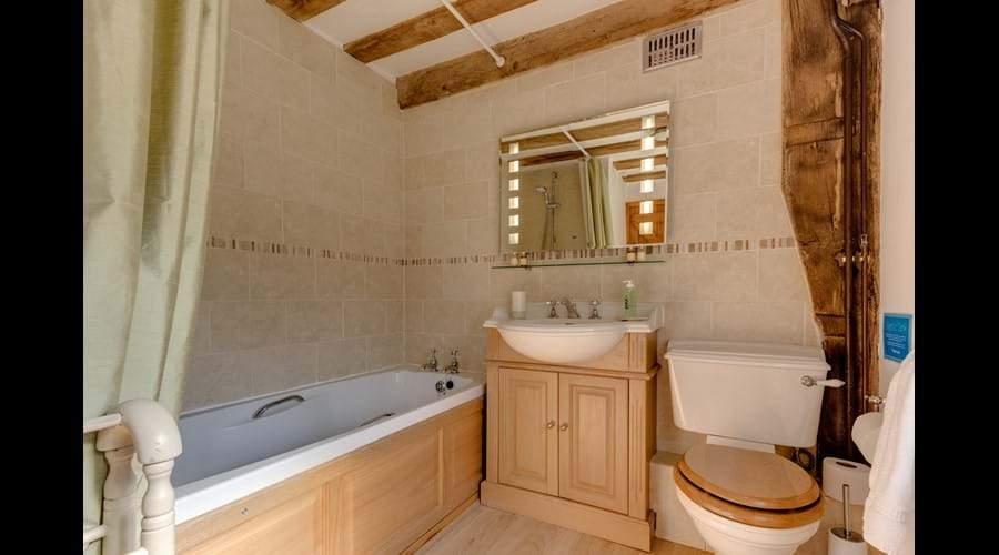 Family bathroom with over-bath power shower and magic heated mirror whose lights turn on at the wave of a hand...