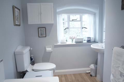 The bathroom lies off the landing, between the two bedrooms upstairs.