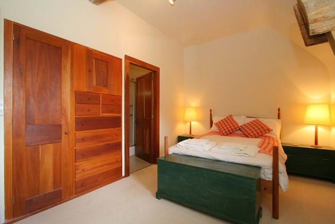 One of two en suite double bedrooms in The Barn, Boudet, Normandy with beautiful handmade wardrobe and chest of drawers.  The en suite has a shower, basin and WC.