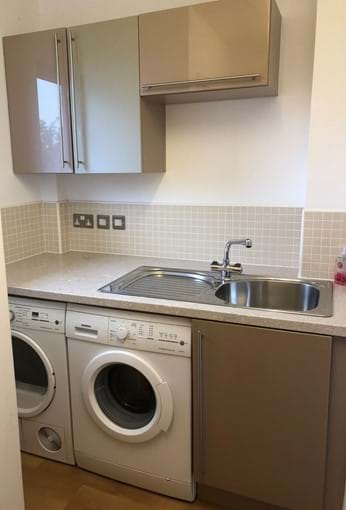 Separate utility room with washing machine and tumble dryer