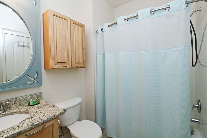 Bathroom 2 at 13-102.  Shower over bathtub, toilet and washbasin.  Granite top