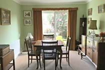 Dining area with walnut furniture over looking garden.