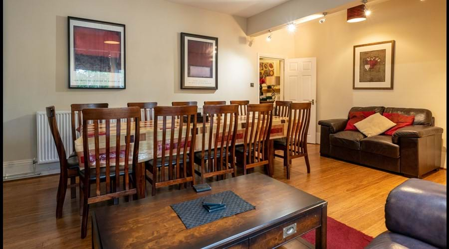 Lower ground floor dining room with hardwood table seating up to 12 people, 2 sofas and coffee table.