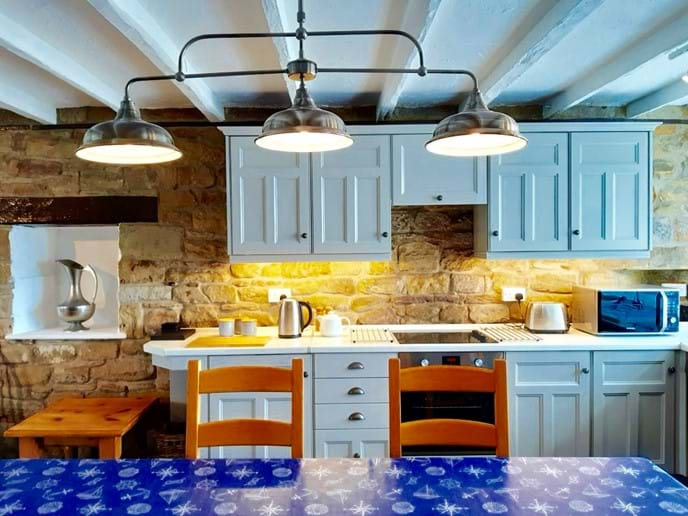 The kitchen has a traditional feel and is fully equipped - the large dining table is lit by an overhead lantern. All lighting is dimmable to create the perfect atmosphere