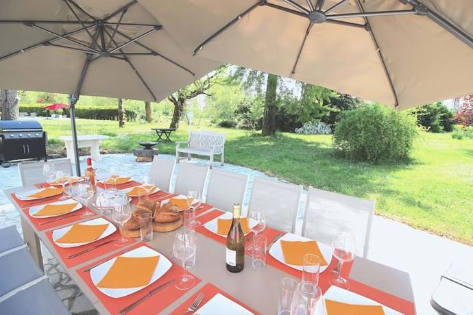 Dining for 12 on the spacious terrace looking over the large garden at Les Arbres