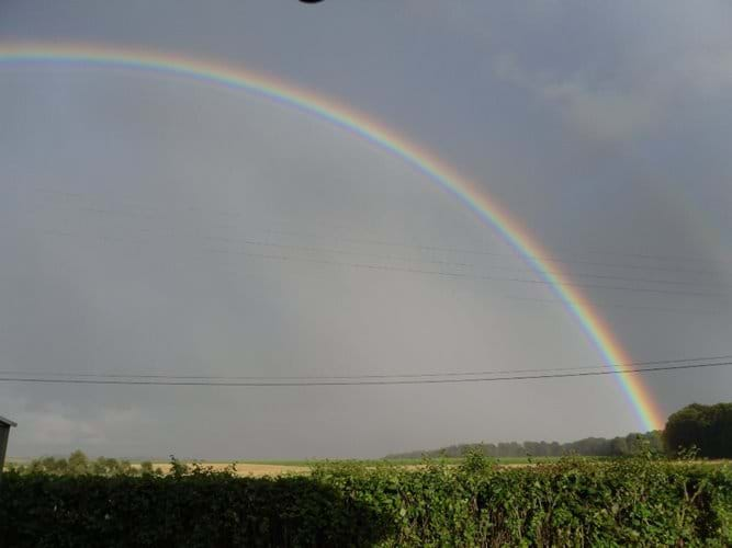 a rainbow as seen across the fields from the kitchen window