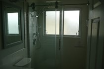 newly remodelled family bathroom with new vanity, mirrors, lights and large shower with seperate handspray
