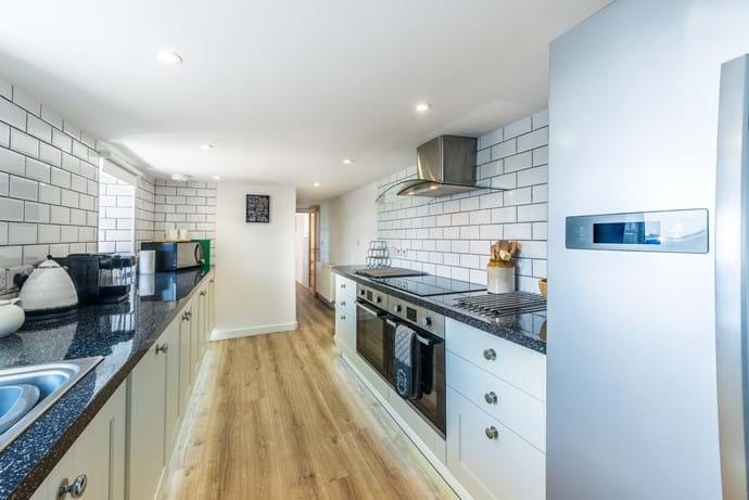 Kitchen with twin fan ovens, halogen hob, American Fridge freezer & dishwasher
