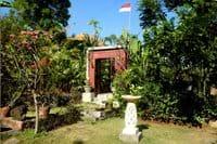 Poort naar terras en zwembad. Dak van tuinhuisje is zichtbaar.