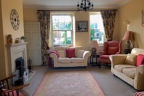The cosy sitting room with open log fire and smart tv