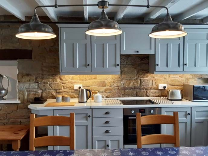 The kitchen has a traditional feel and is fully equipped - there is a large dining table lit by an overhead lantern. All lighting is dimmable to create the perfect atmosphere