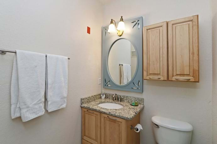 Master Bathroom with Disney Princess Mirror, shower over bathtub, toilet and washbasin.  4 bedroom condo 13-102