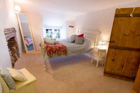 A double bedroom in a North Devon holiday cottage withbedside tables and old oak doors