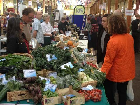 Shoppers view local produce at a market vegetable stall in Barnstaple, Devon