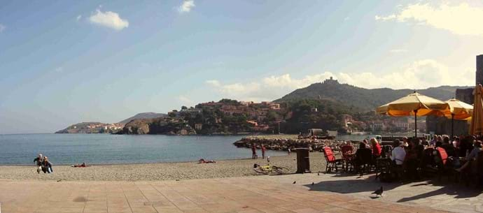 Collioure - Beachside restaurants and across the bay. Sunbathing and still bustling in November. Relax in the sun with a drink or a meal and watch the world go by.