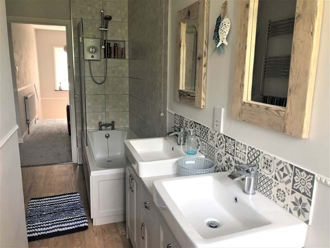 Family bathroom with shower over bath and double sinks