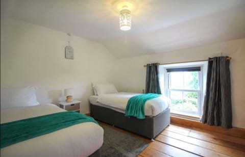 Twin bedroom with wooden floors and soft slate grey rug