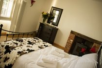 Benbow Cottage - Double bedroom with wrought iron bedstead and solid oak furnishings