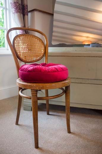 A chair with a scarlet cushion stands in front of a dressing table in a country cottage bedroom
