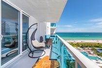 """Two comfortable swing chairs admire the fantastic South Beach View! """