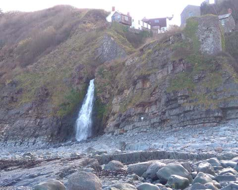 The dramatic waterfall from Bucks Mill onto the beach.