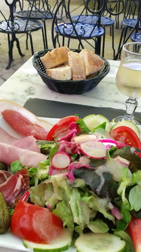 Perigord salad with duck, ham, tomatoes, lettuce and cucumber on plate on table with bowl of french bread and glass of white wine