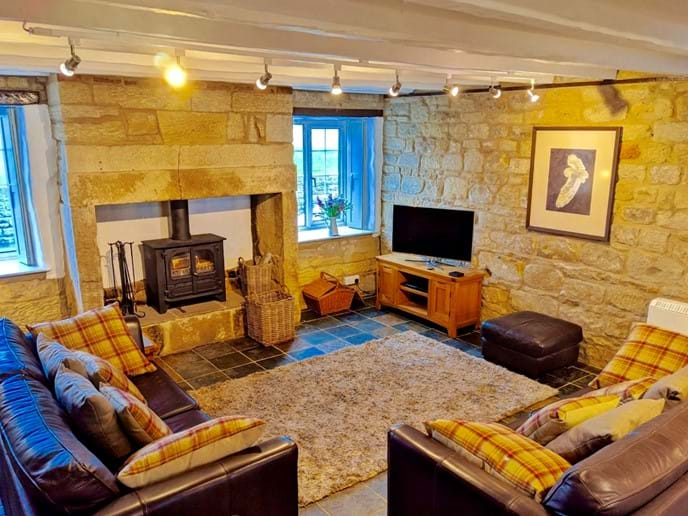 The living area is beautifully furnished with large leather sofas. There is a smart TV with DVD