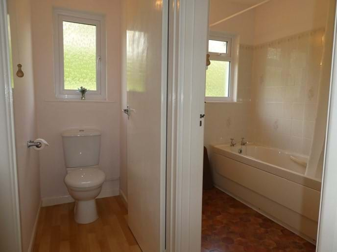 Bathroom with overhead shower and separate toilet