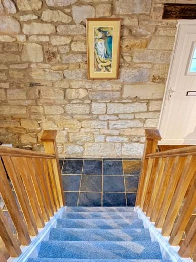 The wooden staircase complements the slate floor and stone walls