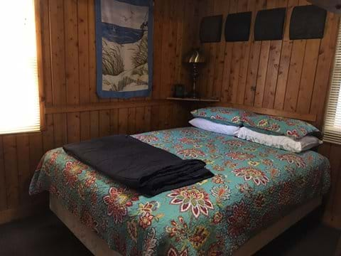 Bedroom with Queen size mattress, quilt, comforter, pillows and blankets.