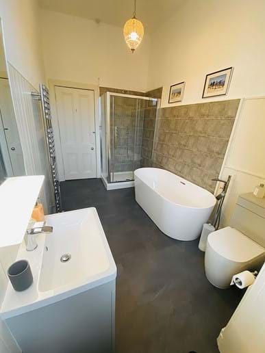 Newly fitted family bathroom with bluetooth speaker mirror, double shower and free standing bath