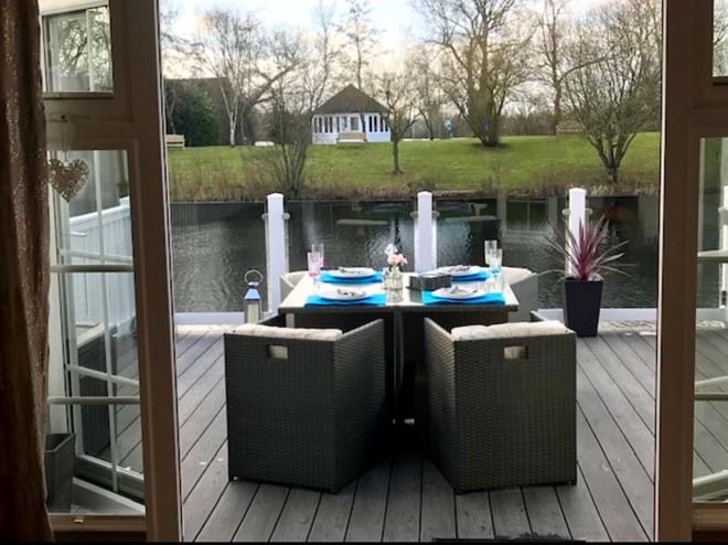 Outside seating overlooking the lake, enclosed decking area with BBQ and patio heater