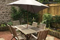 Cosy, private, fenced garden space with dining table for six.