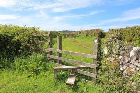 A style and footpath for walkers through a field in North Devon