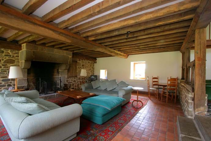 The sitting room in Barn at Boudet, Normandy, France - with comfy sofas, an open fire, English TV, DVD player, docking station, games area, desk and wi-fia luxurious 8 bedroom holiday home in the heart of the countryside