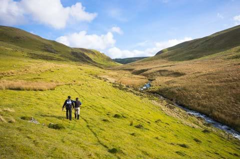 View of two people walking in the Cambrian Mountains with a river to their right