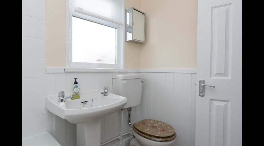 Modern bathroom with electric shower over bath