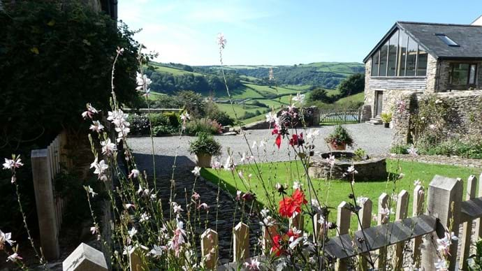 View across the garden to the countryside beyond from Nutcombe Barn terrace