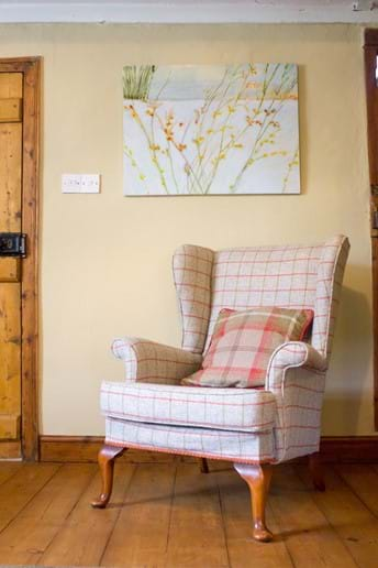 Comfortable reading chair on a pine floored Devon cottage lounge beneath an oil painting