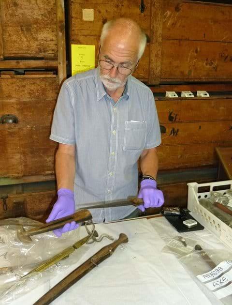 Examining African weaponry, Powell-Cotton Museum storeroom