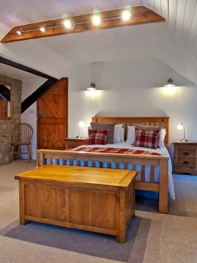 The master bedroom is enormous, with a king sized bed, traditional oak furniture and dimmable lighting