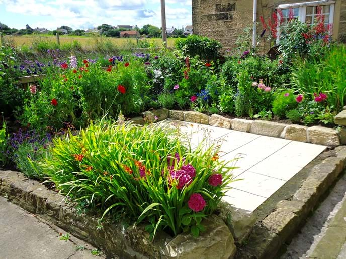 The front garden is a typical cottage garden, bursting with colour in the summer