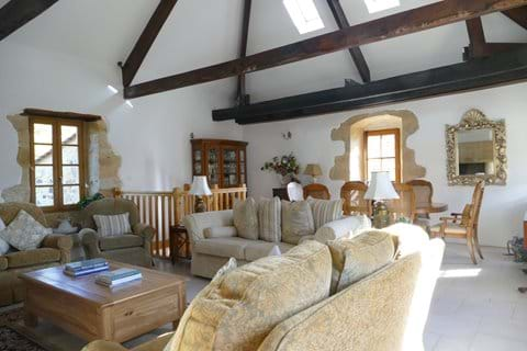 Beautiful large sitting/dining room with exposed beams and stone fireplace