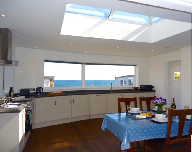The kitchen/diner in Anchor Cottage is huge, light and airy, with a roof lantern and a spectacular sea view
