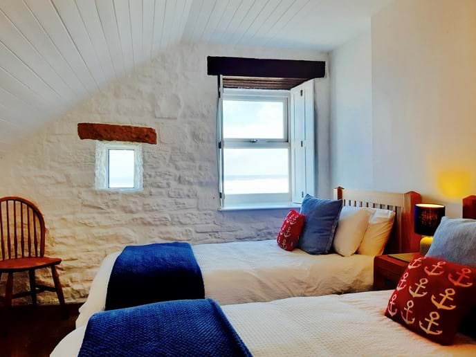 The second bedroom has comfortable twin oak beds furnished with quality linen, and a spectacular sea view